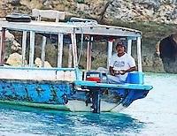 A boat pilot quietly fishing off Pemateran island, Bali, Indonesia.