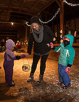 Susan Bosk helps Maya and Chloe Bosk with their lanterns at Prescott Farm during the Lantern Festival on Saturday evening.  (Karen Bobotas/for the Laconia Daily Sun)