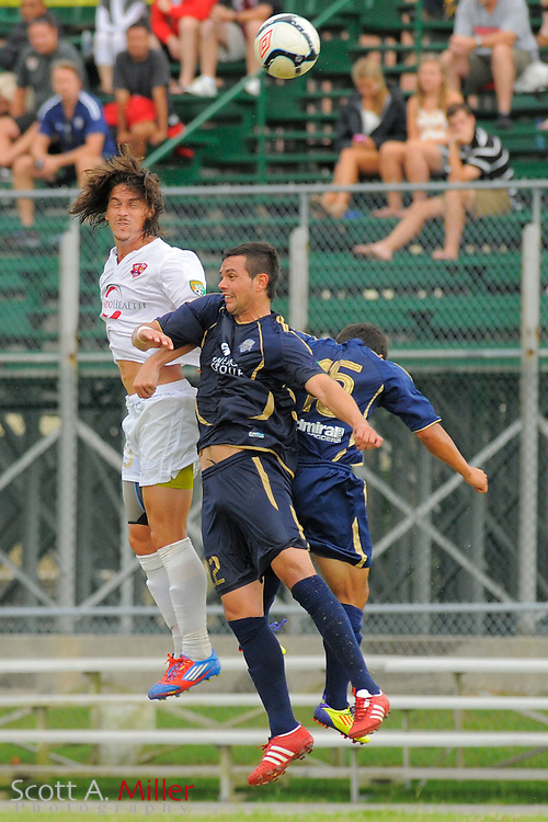 Orlando City forward Drew Helm (23) goes airborne for a ball with Austin Aztex midfielder Franz Justin (22) and Austin Aztex midfielder Jesus Cortes (15) during City's 4-1 win over the Aztex in the PDL Southern Conference Championships final at Trinity Catholic High Schooll on July 22, 2012 in Ocala, Florida. ..©2012 Emily A. Miller