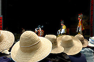 The troup is perforrming in front of an audience of peasants wearing straw hats.