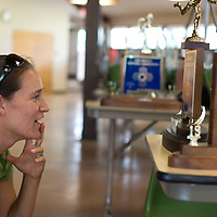 080214      Cayla Nimmo<br /> <br /> Autumn Newell reads the details of the first trophy ever won by the cross country team at Rehoboth High School on Saturday during a reunion. Newell ran for the school from '93-'97. She will take over as head coach for the team beginning this school year.