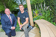 Matthew Keightley (r) and Tom Stimpson   MBE. RAF Veteran on the Hope on the Horizon garden.  The<br /> &lsquo;Hope on the Horizon&rsquo; garden in aid of Help for Heroes: produced by building and landscaping firm Farr and Roberts&rsquo;, making their debut; designed by Matthew Keightley (29), as a result of his brother Michael&rsquo;s involvement with the armed forces, having served on four tours to Afghanistan and due for his fifth this year; and sponsored by the David Brownlow charitable foundation. The garden layout is based on the shape of the Military Cross, the medal awarded for extreme bravery. Granite blocks will represent the soldiers&rsquo; physical wellbeing and the planting represents their psychological wellbeing at various stages of their rehabilitation. Both evolve through the garden from a rough, unfinished, over-grown beginning through to a perfectly sawn, structured end. An avenue of hornbeams draws the attention through the entire garden to a sculpture resembling a hopeful horizon; a reminder to the soldiers that they all have a bright future ahead. As well as areas to recline and reflect, the garden offers focal points all the way through. Cool, calming colours are used throughout, helping to emphasise the fact that it will be a serene, contemplative space. After the Show, the garden will be moved and set within the grounds at Help for Heroes Recovery Centre at Chavasse VC House in Colchester, Essex. The garden will offer a serene, peaceful haven to contemplate and inspire a bright future and to support the challenging journey to recovery. The Chelsea Flower Show 2014. The Royal Hospital, Chelsea, London, UK