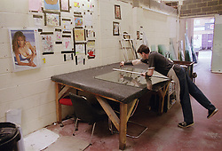 Man working in glass factory measuring piece of glass,
