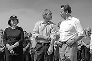 U.S. President George W. Bush rolls up his sleeves as he, California Governor Arnold Schwarzenegger and U.S. Senator Dianne Feinstein (D-CA) hold a news conference on an inspection tour of wildfire damage and response in Redding, California.