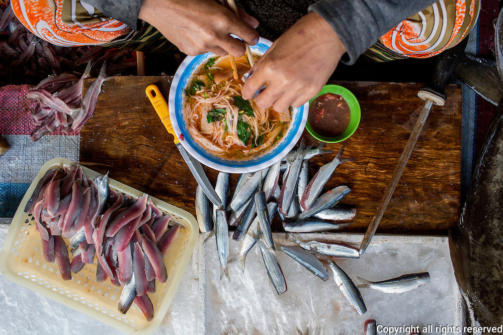 a seller of sardine fillet eats breakfast at her stall at the Duong Dong morning market, Phuc Quoc, Vietnam