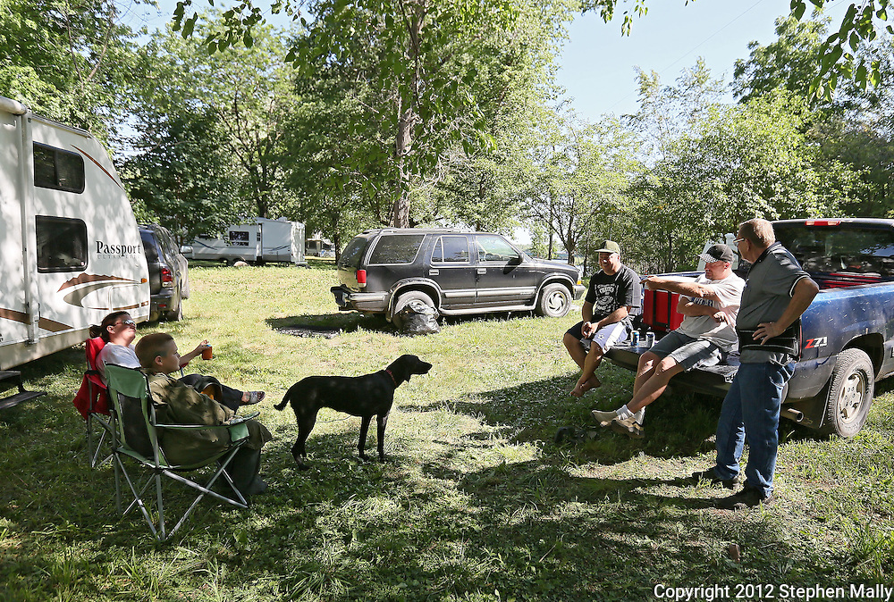 Carolyn Scolaro (from left), Tony Scolaro, 12, Dave Boyle, Cal Schultz, and Dale Bruening, all of Cedar Rapids, talk together at a campground near Bertram on Tuesday afternoon, May 29, 2012. (Stephen Mally/Freelance)