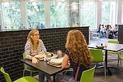 Adrienne Erford and Oliva Dykes have a conversation while finishing their lunch at the new Boyd Dinning Hall.