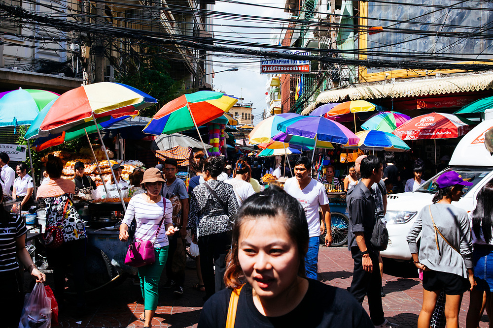 Crowds of people walk through the small alleyways in Chinatown in Bangkok, Thailand.