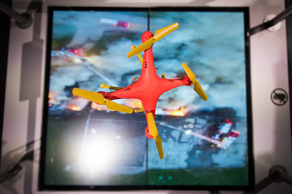 "30206010A - DRONES - A small model drone in orange and yellow colors is held above a video of a building fire to show the use of drones to evaluate dangerous situations from different angles at the ""Drones: Is the Sky the Limit?"" exhibit at the Intrepid Sea, Air, and Space Museum in New York, NY on May 9, 2017."