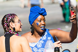 London, August 27 2017. A woman takes a quick selfie as she get makeup applies as Family Day of the Notting Hill Carnival gets underway. The Notting Hill Carnival is Europe's biggest street party held over two days of the bank holiday weekend, attracting over a million people. © Paul Davey.