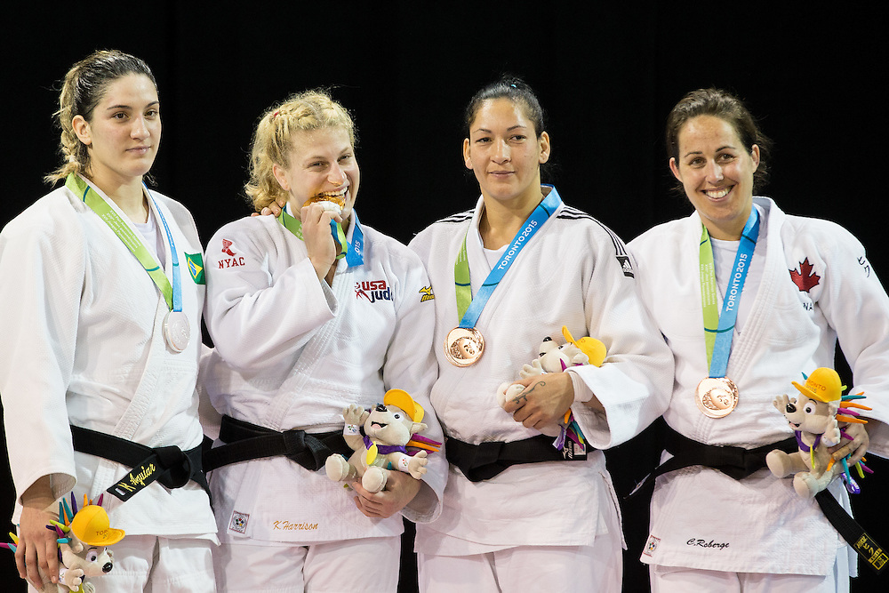 Gold medalist  Kayla Harrison of the United States  bites her medal as she and her fellow medal winners (L-R) silver medalist  Mayra Aguiar, bronze medalists Yalennis Castillo of Cuba and Catherine Roberge of Canada gather on the podium during the medal ceremonies at the 2015 Pan American Games in Toronto, Canada, July 14,  2015.  AFP PHOTO/GEOFF ROBINS