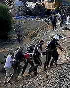 LAPD officers carry a victim up to the train tracks. Behind them, rescue workers work to remove victims who were traped inside the wreckage of a MetroLink commuter train that collided with a freight train in Chatsworth, California that claimed 25 lives on Friday, Sept. 12, 2008. Photo by John McCoy/staff photographer.