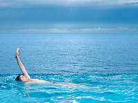 man swimming in a beautiful swimming pool by the seaside