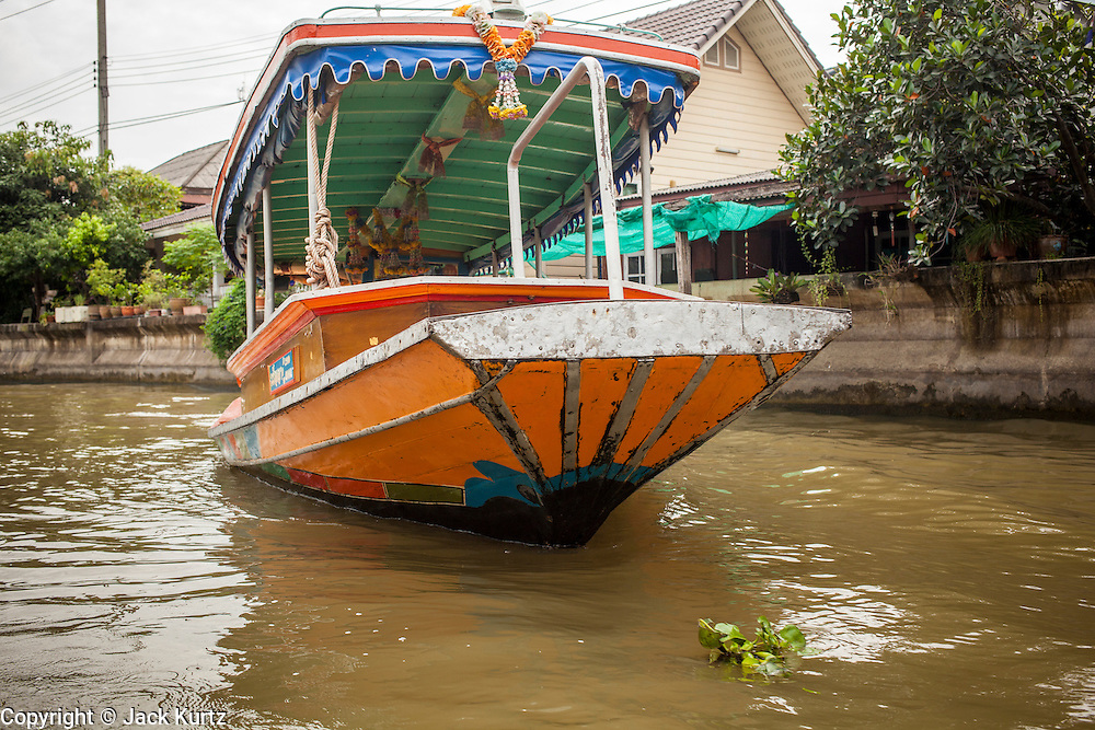 """17 NOVEMBER 2012 - BANGKOK, THAILAND:  A river taxi on a khlong or canal in the Thonburi section of Bangkok. Bangkok used to be known as the """"Venice of the East"""" because of the number of waterways the criss crossed the city. Now most of the waterways have been filled in but boats and ships still play an important role in daily life in Bangkok. Thousands of people commute to work daily on the Chao Phraya Express Boats and fast boats that ply Khlong Saen Saeb or use boats to get around on the canals on the Thonburi side of the river. Boats are used to haul commodities through the city to deep water ports for export.    PHOTO BY JACK KURTZ"""