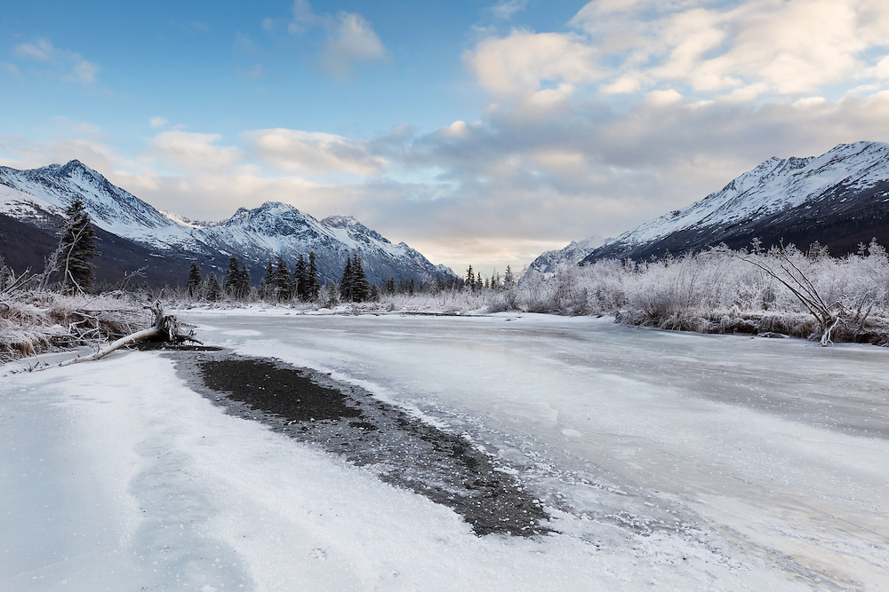 Hoar frost along frozen Eagle River in Chugach State Park with Chugach Mountains in background in Southcentral Alaska. Afternoon. Winter.