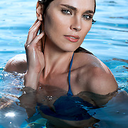Portrait of a young beautiful woman submerged in water up to her chest and looking sultry.