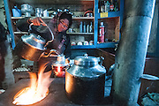 Nepal, Annapurna Region, Nar village. the kitchen inside a guest house. A woman is pouring tea into a thermos.