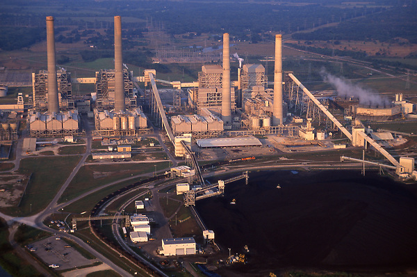 Stock photo of the aerial view of a chemical plant on the shore at dusk