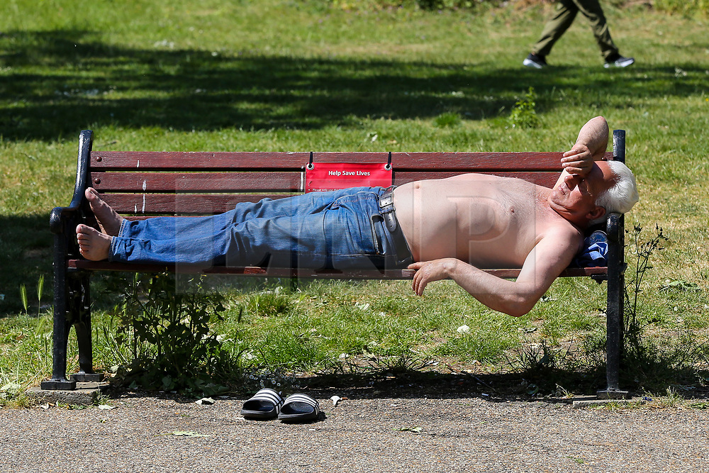 © Licensed to London News Pictures. 25/05/2020. London, UK. A man sleeping on a park bench in Finsbury Park, north London on a warm and sunny Bank Holiday. The government has relaxed the rules during the COVID-19 lockdown, allowing people to spend more time outside to enjoy sunbathing and picnicking whilst following social distancing guidelines. According to the Met Office, warmer temperatures are forecast with highs of 25 degrees celsius.  <br /> Photo credit: Dinendra Haria/LNP