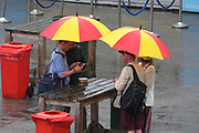 Spectators sheltering from the heavy rain in under umbrellas behind the Edrich Stand ahead of the International Test Match 2019 match between England and Australia at Lord's Cricket Ground, St John's Wood, United Kingdom on 18 August 2019.