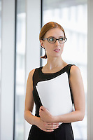 Thoughtful businesswoman holding documents in office