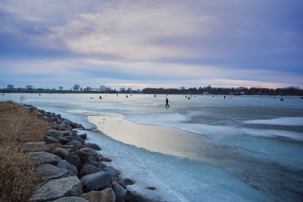 2016, Winter. Early morning people ice fishing on Lake Monona. Several people sitting out at the North Triangle by Brittingham Bay close to by John Nolen Drive and North Shore Drive, in Madison, Wisconsin.
