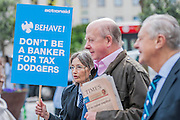 Protestors complaining about the use of tax havens (pictured), banks support for coal mining and the lack of a robin hood tax on financial transactions gather outside the Festival Hall as Barclays plc shareholders queue for the bank's AGM. Southbank, London, UK 24 April 2014.