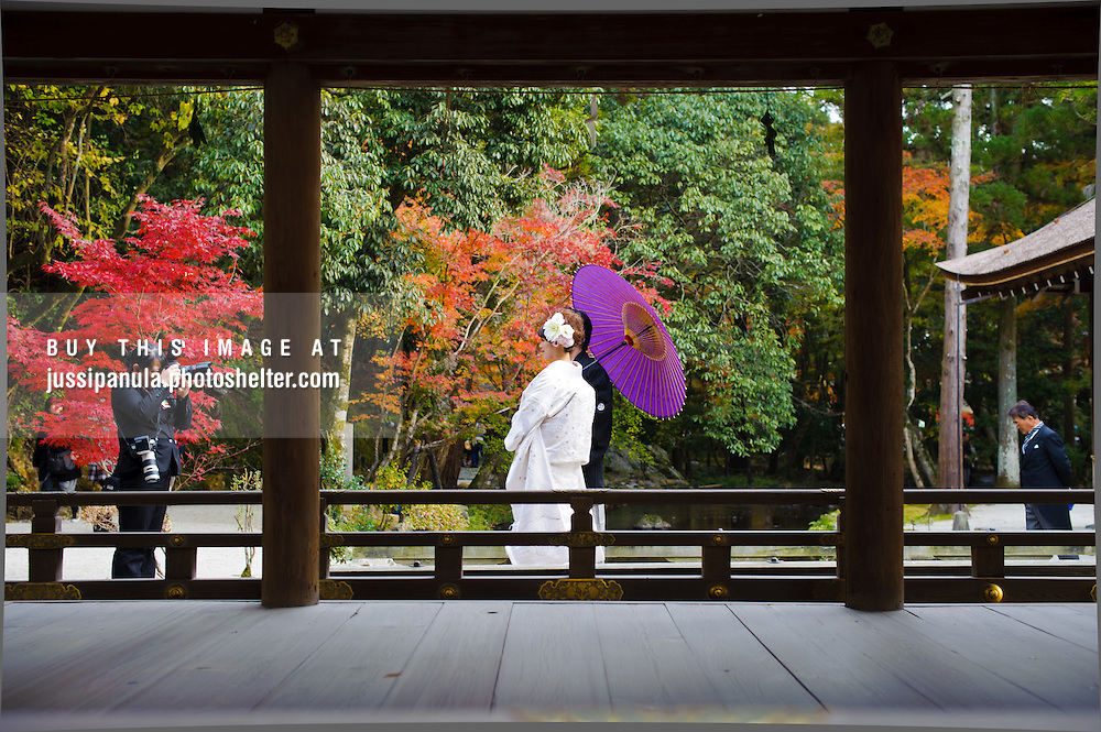 A married couple being photographed after the ceremony at Kamigamo Shrine, Kyoto, Japan. Photographed in early autumn.