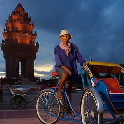 A cyclo driver poses for a portrait in front of the victory monument in Phnom Penh, Cambodia.