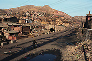 A coal miner pushes a bicycle through mine worker's housing toward a coal mine in the region known as the &quot;sea of coal.&quot; 75% of China's growing energy needs is supplied by coal, the cheapest and dirtiest form of energy. China is the world's largest producer of coal. Seven of the world's ten most polluted cities are in China, largely due to coal use and the country's dilapidated heavy industries.<br /> D&agrave;t&oacute;ng, Shanxi Province, China. 12/11/2005<br /> Photo &copy; J.B. Russell