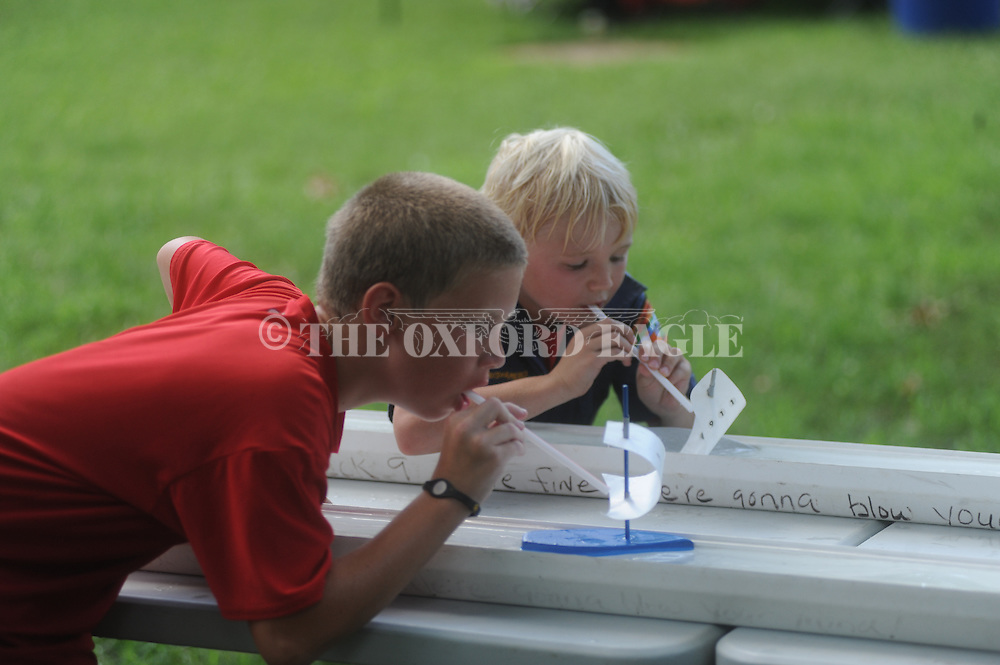 George Moak (red) and Bailey Quin (blue) race sail boats as the Boy Scouts celebrated their 100th birthday in the Grove at Ole Miss in Oxford, Miss. on Saturday, July 31, 2010.