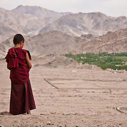 Young buddhist looks out over the valley from the Thiksey Gompa.
