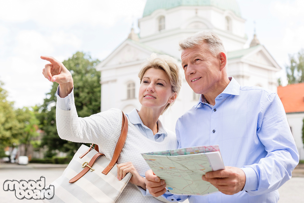 Middle-aged woman showing something to man holding map outdoors