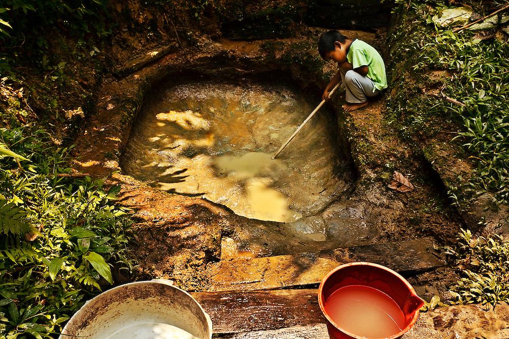 Colombia, Macedonia, 2010. Un pozo con fin. <br /> Cuando llega la &eacute;poca seca del a&ntilde;o y no llueve, los pobladores improvisan pozos artesanales para recoger agua pura. En medio de tal abundancia de vida, en esta selva se corre el riesgo de no proporcionar el agua suficiente para el consumo humano. Las consecuencias del uso del hombre sobre los recursos naturales y el cambio clim&aacute;tico se tornan m&aacute;s dr&aacute;sticas en este paisaje virgen. <br /> . A well with aim.<br /> When the dry season arrives and it does not rain, the villagers improvise by building artisan wells to gather pure water. In the middle of such abundant life, this forest runs the risk of not providing sufficient drinking water for its humans&rsquo; consumption. The consequences of man&rsquo;s use of the natural resources and its effect on climatic changes become more dramatic in this virgin landscape.