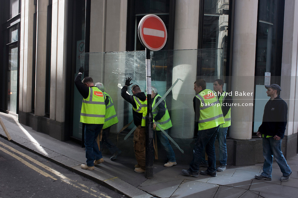 A team of labourers struggle to manhandle a very heavy plate-glass window through a City of London street.