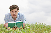 Portrait of young man holding book while lying on grass against sky