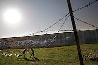 ©WEST BANK 2007. Children playing football next to the separation wall, Qalqilya..Picture featured in book KIDS photos by Markus Marcetic, published 2007.