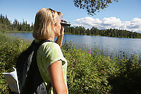 USA, Alaska, woman looking through binoculars at lake