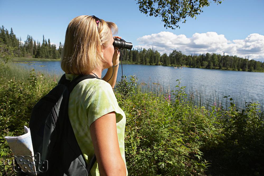USA, Alaska, woman looking through binoculars at lake
