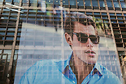 With corporate offices reflected in the window, an image of a male model looks out of the window of a menswear retailer near Liverpool Street Station in the City of London, the capital's financial district - aka the Square Mile, on 8th August, in London, England.