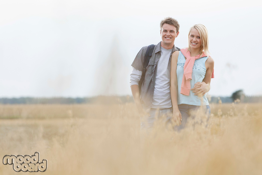 Happy young couple standing at field