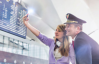 Young beautiful teenage girl taking selfie with mature pilot in airport