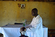 Manomano Village, Zimbabwe, November, 2012. Ismael Khumalo in prayer with a congruent at his church. Ismael says his animist church is growing because many people have fled the Salvation Army Church after the transfer in August, 2012  of a popular Howard Hospital doctor.
