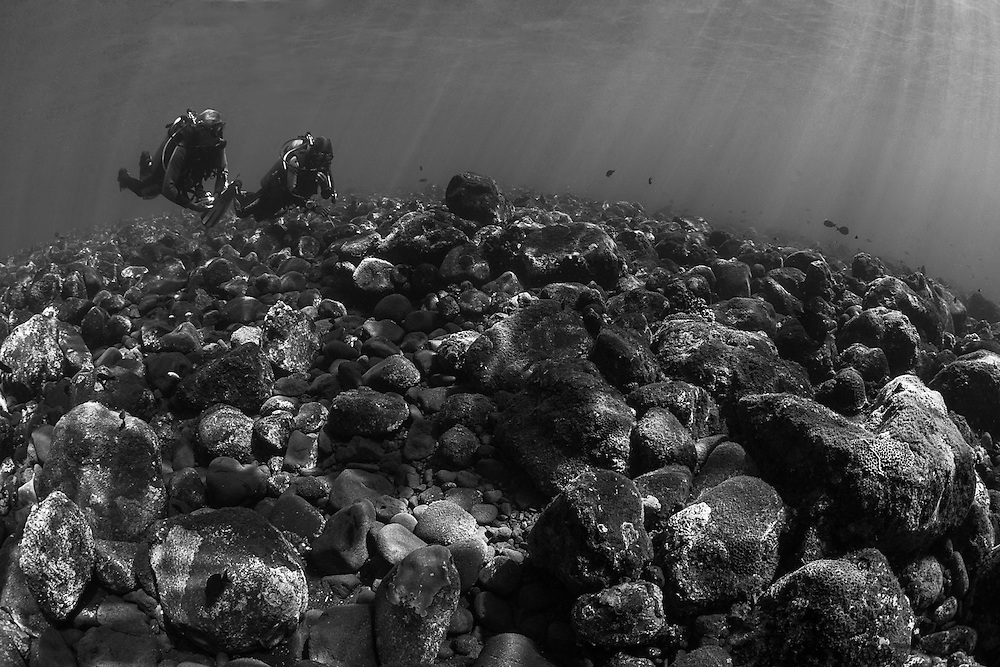 INDONESIA. Tulamben, Bali. July 8th, 2013. Two divers, just after sunrise, begin to descend over the steep reef slope at a dive site named Drop Off.