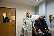 Dr. Tony Hampton, with Advocate Health, talks with medical staff Lauren Hayes, (left) after examining Willie Davis, 65, who was complaing about an injury to his rib cage during a visit at the Beverly Medical Building in Chicago on Tuesday, November 12, 2013. Nathan Weber for ProPublica