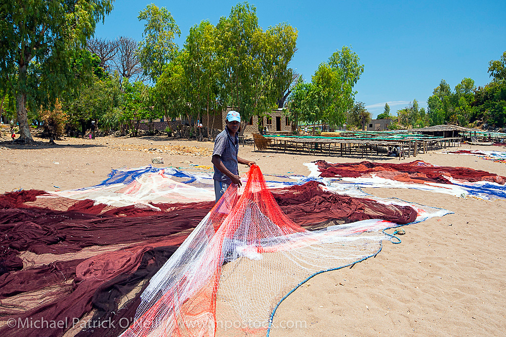 A fisherman tends his nets on the beach in Chizimulu Island, Lake Malawi, Malawi, Africa.