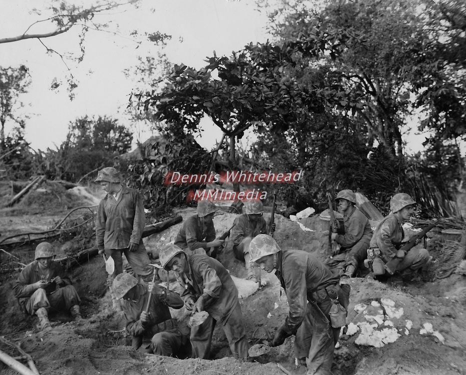 While enemy mortar shells scream overhead, Marines prepare for their first night on Saipan. Weapons are cleaned and foxholes dug in preparation for the anticipated counter-attack by the Japanese.