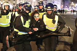 © Licensed to London News Pictures . 05/11/2016 . London , UK . Police detain, handcuff and carry away a woman in Trafalgar Square. Supporters of Anonymous , many wearing Guy Fawkes masks , attend the Million Mask March bonfire night demonstration , in central London . Photo credit : Joel Goodman/LNP