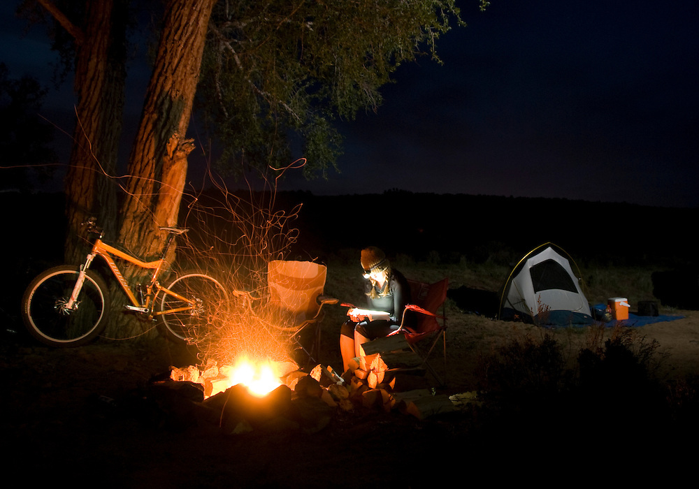 Reading by the firelight at desert singletrack base camp.