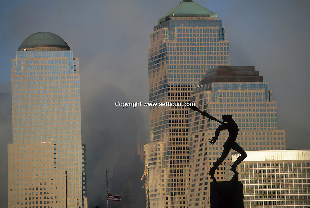 New York 9/11.  september 11 2001, attack terrorist on world trade center towers in Manhattan. view from New Jersey , in front the  sculpture to the victims of Katyn  New york  Usa   /   9/11 11 septembre 2001 attaque terroriste sur les tours du world trade center a Manhattan, vue depuis New Jersey devant le monument aux victimes de Katyn assassines dans le dos lachement  New york  USA